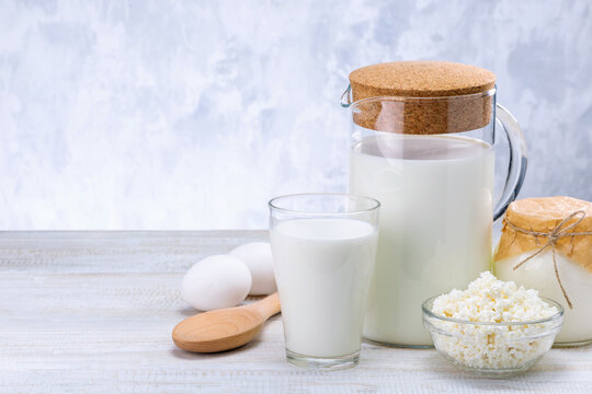 Dairy Products, Milk, Cottage Cheese, Eggs And Sour Cream On Wooden Table Against Grey Wall With Copy Space.