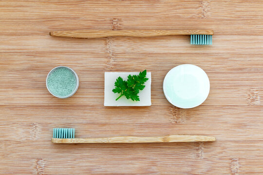 Zero waste bathroom basics. Bamboo toothbrushes,  solid toothpaste in metal tin, solid shampoo and soap on wood background. Plastic free, environment concept.