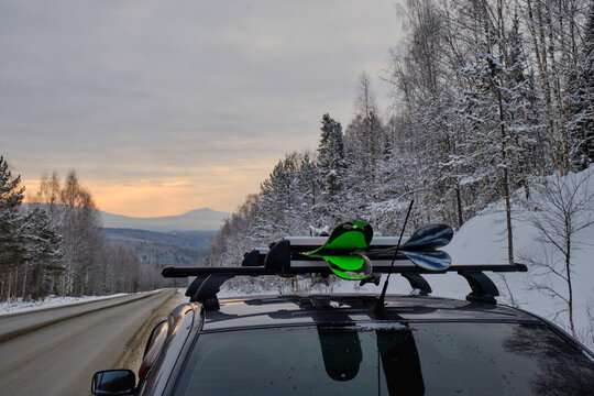 Roof rack of a ski and snowboard car with a mountain background in winter