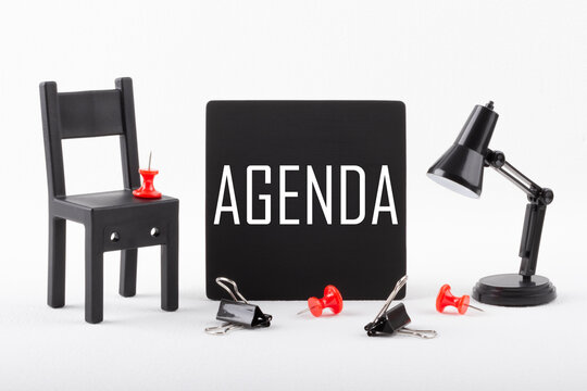 Text AGENDA on a black chalkboard next to a miniature chair and lamp on a white background. Business concept.