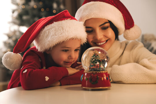Mother and daughter in Santa hats playing with snow globe at table