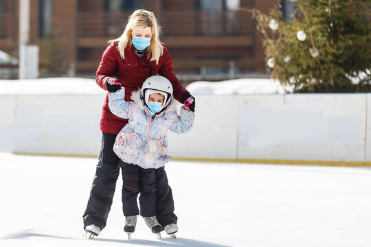 young mother teaching her little daughter ice skating at outdoor skating rink. Family wearing a medical mask during COVID-19 coronavirus enjoy winter on ice-rink outdoors