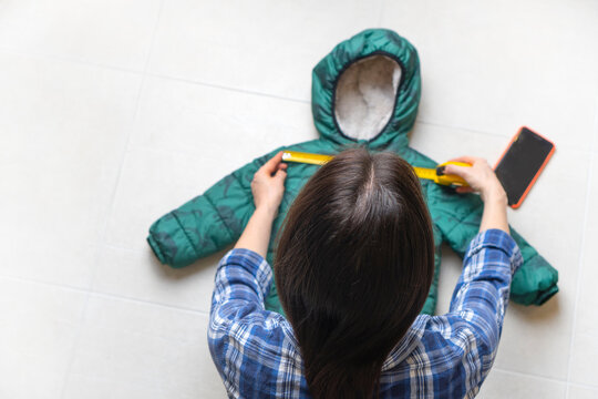 Mom measures the baby's jacket with a tape measure. View above.