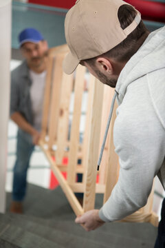 two male movers carrying the empty shelf on the staircase