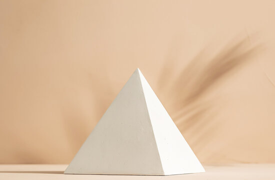 Gypsum pyramid in sunlight and palm leaf shadow on clay wall background