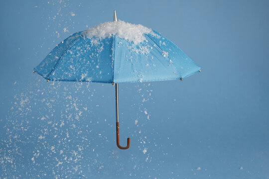 Blue umbrella on blue background with snow. Blue monday concept.