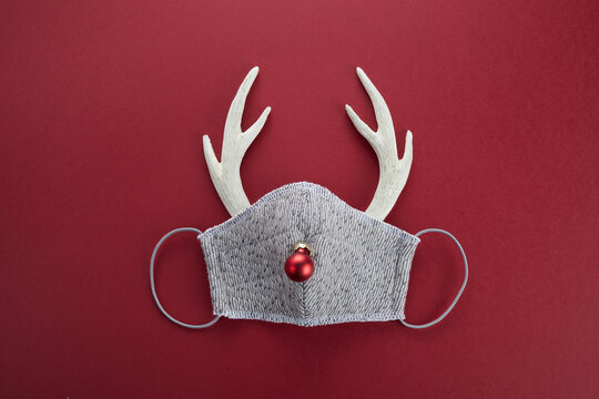 Reindeer horns with face mask and red ball. Pandemic Christmas concept. Flat lay.