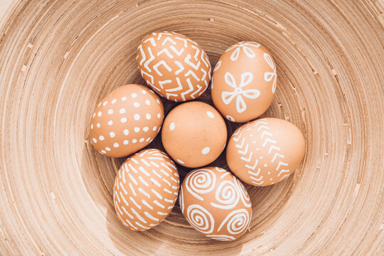 Easter eggs hand-painted with white patterns in a bamboo dish