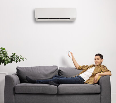 Young man sitting on a sofa and putting an air conditioning unit on with a remote control