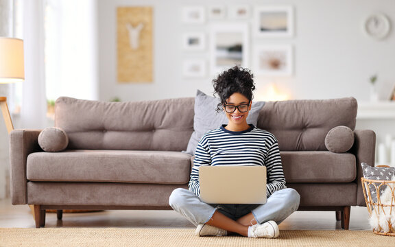 Joyful relaxed ethnic woman using laptop with interest at home.