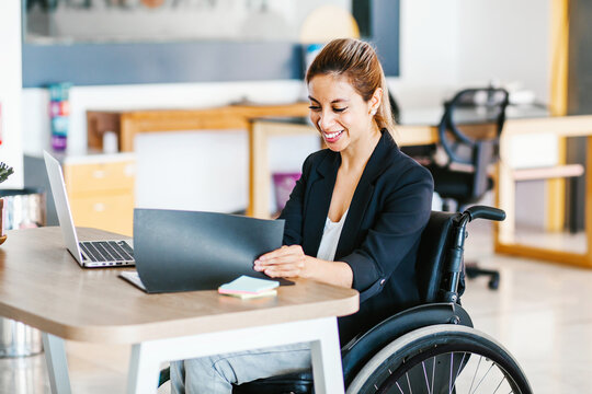 Disabled Hispanic female sitting at office desk, working on laptop in Mexico City
