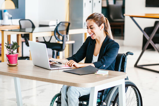 Disabled mexican female sitting at office desk, working on laptop in Mexico City