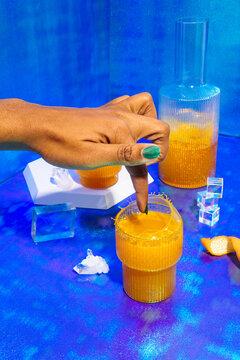 Woman's finger stirring kombucha cocktail