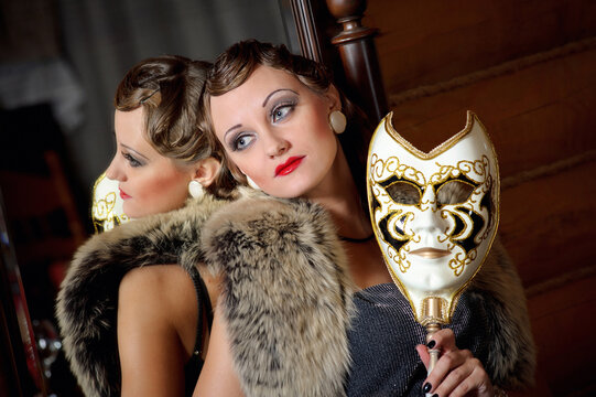 Beautiful retro woman with mask near the mirror. Old fashioned vintage makeup and wavy hairstyle. Hollywood style of the 20s
