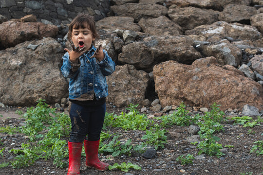A little girl looking at her hands covered in mud