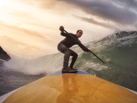 Adventurous Man Surfing the waves at the Pacific Ocean in Oregon Coast. Dramatic Colorful Sunrise Sky. Extreme sport