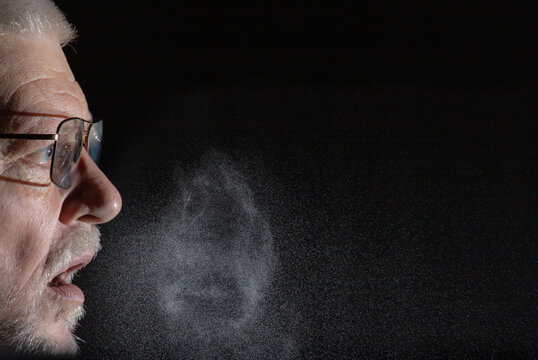 A man sprays aerosols into the air while speaking. The background is black.