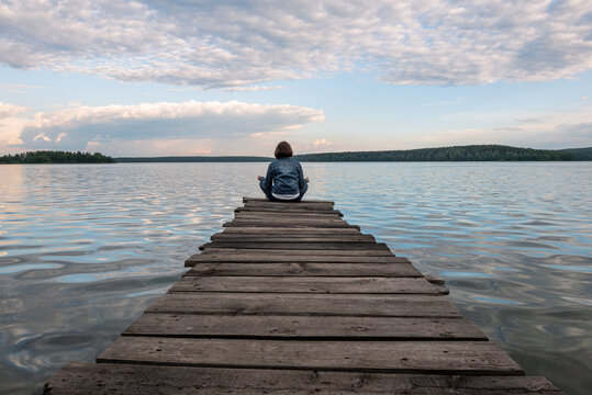 Girl sitting in lotus position on a wooden pier