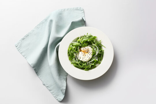 Plate with tasty arugula salad on white background