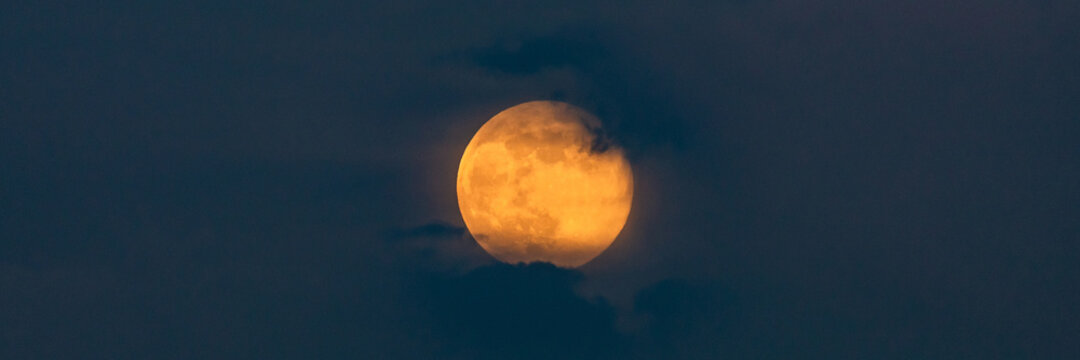 Bright Yellow Full Moon in clouds