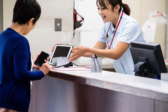 病院代の支払いをスマートフォンで済ませている高齢の女性