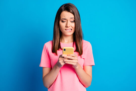 Photo portrait of stressed female student reading information in internet isolated on bright blue color background