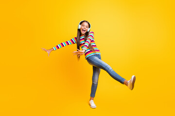 Full length body size photo of careless playful cheerful girl with earphones dancing isolated on vibrant yellow color background
