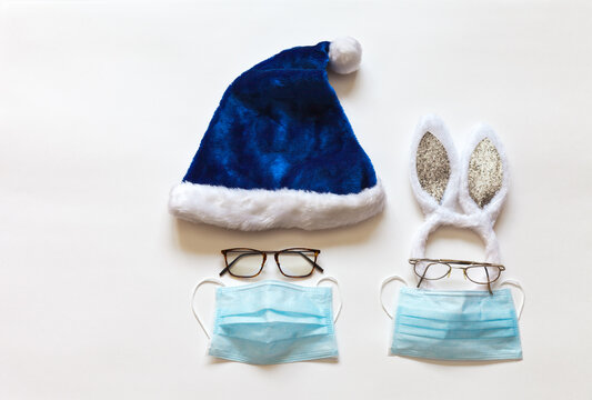 Blue Santa hat and festive bunny ears with goggles and protective medical face masks. Celebrating Christmas and New Years safely during the coronavirus pandemic COVID-19. Safe holidays concept