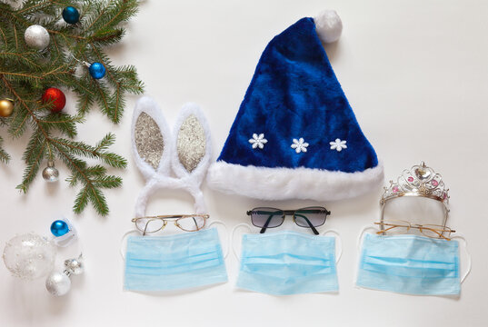 Festive Christmas and New Year's costumes: blue Santa Claus hat, rabbit ears, Snow Maiden crown with protective medical face masks. Celebrating X-Mas safely during the COVID-19 coronavirus pandemic