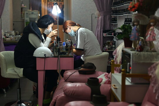 People sit at a nail salon while wearing protective masks to prevent the spread of COVID-19 in Taipei