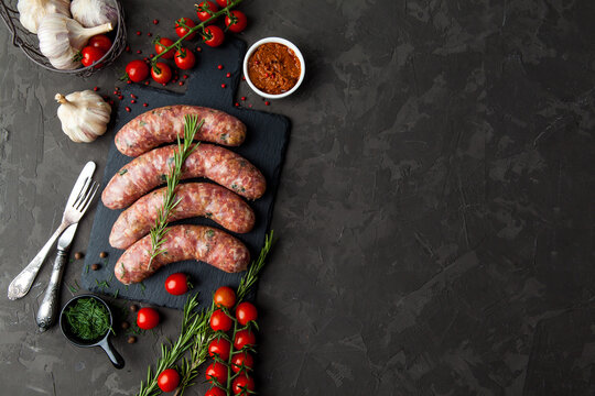 raw sausages with ingredients  in a black background with copy space for text