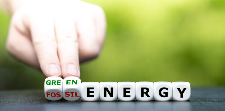 "Hand turns dice and changes the expression ""fossil energy"" to ""green energy""."