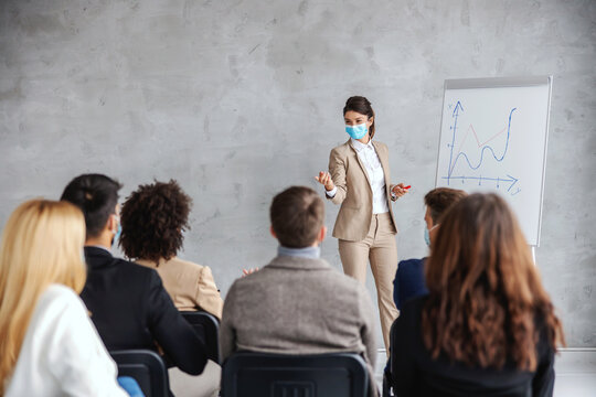 Young businesswoman with face mask standing in front of audience an having presentation of monthly salary on stock. Business during corona virus concept.