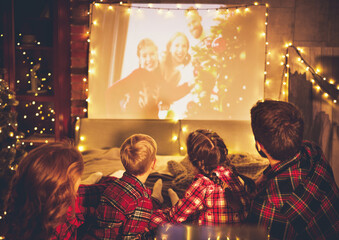 family mother father and children watching projector, TV, movies with popcorn in   christmas...