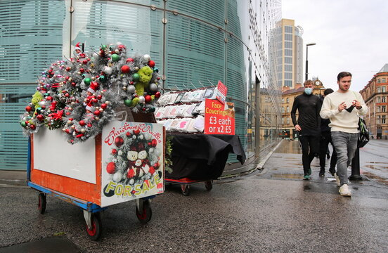People walk past a wreath stall in Manchester