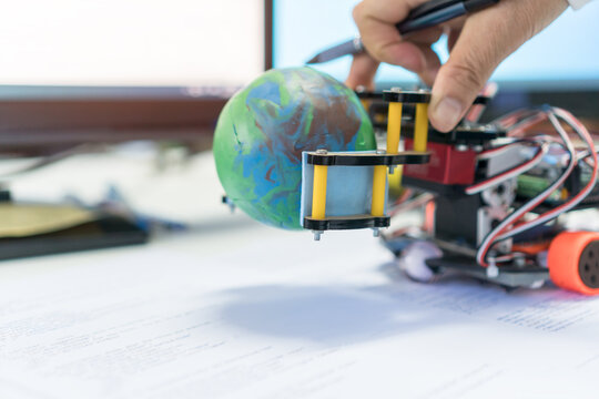 Student learning STEM Education for Learn coding programming with Control robot to pick up model globe by robotics electronics in school, program in technology for innovation futuristic