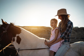 Fototapeta Happy mother and daughter riding a horse at sunset - Family and love concept - Focus on kid face