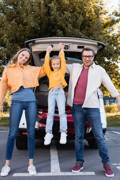 Cheerful parents holding daughter near car outdoors