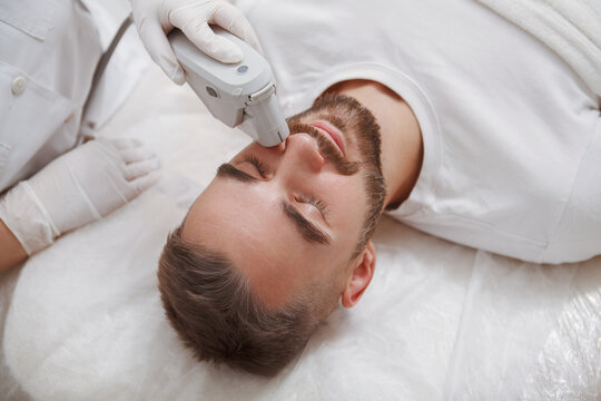 Close up of a bearded man enjoying getting laser facial treatment by professional cosmetologist