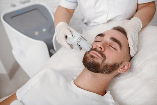 Handsome bearded man getting facial laser treatment by cosmetician