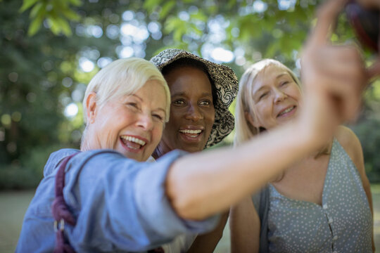 Happy senior women friends taking selfie in park