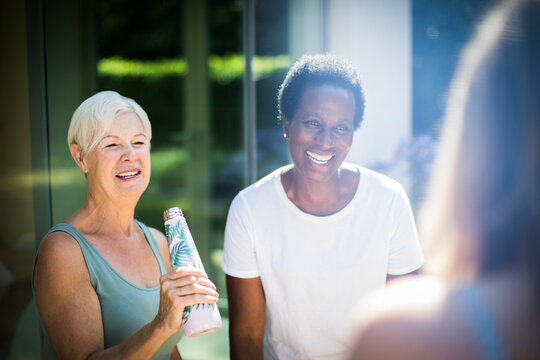 Happy senior women friends laughing on sunny summer patio