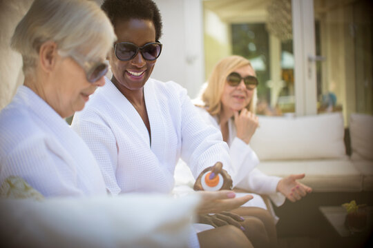 Senior women friends in spa bathrobes and sunglasses on patio