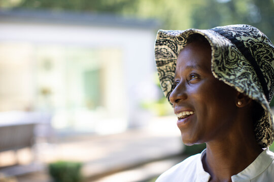 Portrait hopeful happy senior woman in sun hat