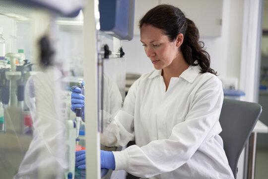 Focused female scientist in lab coat working in laboratory