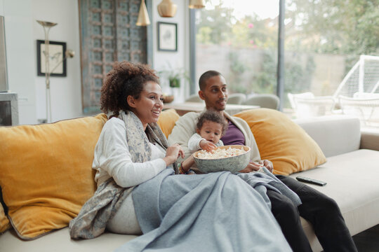 Parents with baby daughter watching movie with popcorn on sofa