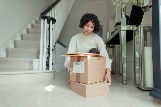 Woman receiving packages stacked on foyer floor