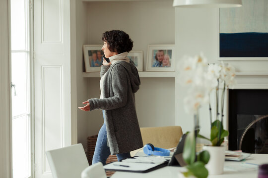 Woman working from home talking on smart phone at window