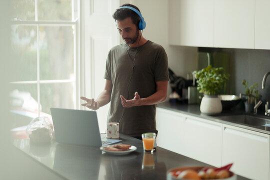 Man with headphones working from home video conferencing at laptop