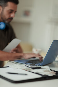 Man with receipts and calculator paying bills at laptop